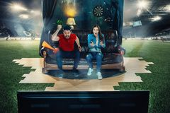 Leidenschaftliche Fans sitzen im dem Sofa und dem aufpassenden Fernsehen mitten in einem Fußballplatz Lizenzfreie Stockfotografie