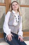 Leidenschaftliche kaukasische blonde Frau, die draußen in der Stadt gegen Fenster-Scheibe aufwirft Stockfotos