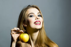 Leidenschaftliche lächelnde blonde junge Frau mit Apfel Lizenzfreie Stockbilder