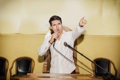 Leidenschaftlicher Mann, der in Mikrofon in der Sitzung spricht Stockbilder