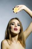 Leidenschaftliches blondes Porträt der jungen Frau mit Orange Stockfotografie