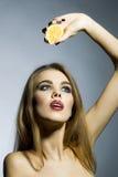 Leidenschaftliches blondes Porträt der jungen Frau mit Orange Lizenzfreie Stockfotos