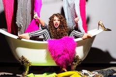 Leidenschaftliches emotionales junges Mädchen mit Kleidung in der Badewanne Lizenzfreie Stockfotografie