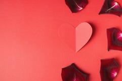 Leidenschaftskonzept für Valentinstag mit den dunklen rosafarbenen Blumenblättern und einem Papierherzen auf einem roten Hintergr Stockbilder