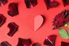 Leidenschaftskonzept für Valentinstag mit dunkelrotem stieg, Blumenblätter und ein Papierherz Stockfotos