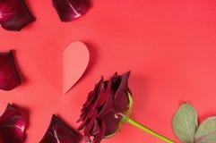 Leidenschaftskonzept für Valentinstag mit dunkelrotem stieg, Blumenblätter und ein Papierherz auf einem roten Hintergrund Stockbild