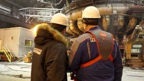 Leider en werknemer bij de fabriek De leider plaatst de taak aan de arbeider stock video