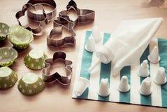 Leidingenzak met koekjessnijders en koppen wordt geplaatst voor cupcakes die Stock Afbeelding
