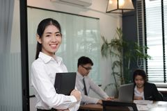 Leidings bedrijfsvrouwenconcept Vrolijke jonge Aziatische onderneemster met ringsbindmiddel die zich tegen haar collega in bureau Royalty-vrije Stock Afbeeldingen