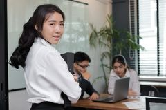 Leidings jonge Aziatische bedrijfsvrouw met ringsbindmiddel die zich tegen haar collega op bureauachtergrond bevinden Royalty-vrije Stock Afbeelding