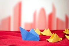 Leidingsconcept in de hoge concurrentie met document boten op rood s Stock Afbeeldingen