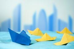 Leidingsconcept in de lage concurrentie met document boten op blauw s Royalty-vrije Stock Foto
