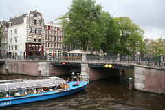 The Leidsegracht populate the canal. Netherlands, Amsterdam, June-2016: A bridge over The Leidsegracht with pedestrians and parked bikes Stock Photos