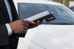 Leihwagenarbeitskraft mit digitalem Notizbuch ein Auto zum Kunden heraus überprüfend Nahaufnahmeernte von Schwarzes bemannt Hände stockbilder