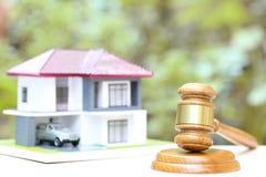 Leilão da propriedade, casa de madeira e modelo do martelo no fundo verde natural, o advogado de bens imobiliários da casa e a pr fotografia de stock