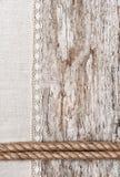 Leinengewebe mit Spitze und Seil auf dem alten Holz Lizenzfreies Stockfoto
