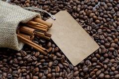 Leinensack mit rohen Bohnen des Zimts und des Kaffees und Verkaufsaufkleber Stockfotos