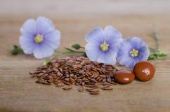 Leinsamen, Schönheitsblume und Pillen woooden an Hintergrund Stockfotografie