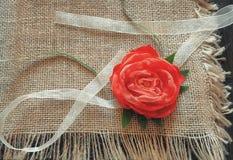 Leinwand wird mit einer roten Rose vom Gewebe mit einem Band verziert Stockfotografie
