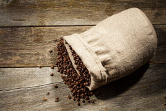 Leinwandsack Kaffeebohnen gegen dunklen hölzernen Hintergrund Lizenzfreies Stockbild
