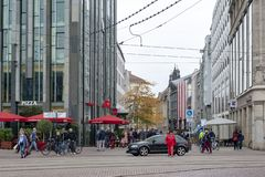 Central business district and city square near Augustusplatz in downtown Leipzig, Germany. Leipzig, Germany - October 2018: Pedestrians on street alongside with stock images