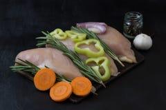 Leiste der Hühnerbrust mit Rosmarin und gehackte Karotten, Pfeffer und Zwiebeln Lizenzfreies Stockbild