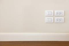 Leistunganschluß und heller Schalter auf der Wand Stockfotografie