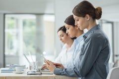 Leistungsfähige Geschäftsfrauen, die zusammenarbeiten Stockfotografie