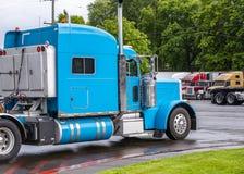 Leistungsfähiger halb LKW-Traktor der klassischen blauen großen Anlage, der an den Ausgang des Fernfahrerrastplatzes auf Straße v lizenzfreie stockbilder