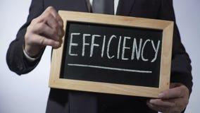 Leistungsfähigkeit geschrieben auf Tafel, Mann im schwarzen Anzug, der Zeichen, Geschäft hält stock footage