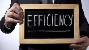 Leistungsfähigkeit geschrieben auf Tafel, Mann im schwarzen Anzug, der Zeichen, Geschäft hält lizenzfreies stockfoto