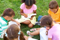At leisure. Portrait of cute kids seated on green grass with copybooks and pencils Stock Photos