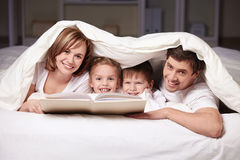 Leisure. Parents and children with a book under a blanket royalty free stock photo