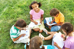 At leisure. Portrait of cute kids seated on green grass with copybooks and pencils Royalty Free Stock Photo