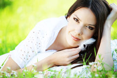 Leisure. Young cute girl resting on soft pillow in fresh spring grass Royalty Free Stock Image