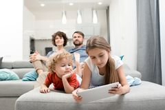 Leisure Activities of Loving Family. Cute little boy and his pretty elder sister lying on sofa and playing game on digital tablet while his parents sitting Royalty Free Stock Image