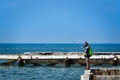 Leisure Activity, A Man Fishing at the Sea. Leisure Activity, A Man Standing on the Bar Fishing at the Sea Stock Photo