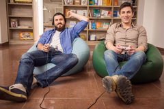 Leisure actvity. Two young handsome guys sitting on poufs and playing video games together. Leisure time stock photos