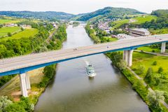 A leisure boat under high bridge where A13 motorway meets 8 highway over Moselle river. Aerial view of Schengen town center. Tripoint of borders of Luxembourg royalty free stock photography