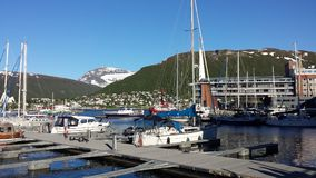 Leisure boats in tromsoe city harbor in bright summer sunshine. With the connecing bridge and tall mountain backdrop stock photo