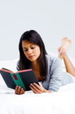 Leisure book woman. Leisure reading woman is comfortable lying on her bed with a book, smiling and happy isolated on grey background Royalty Free Stock Image
