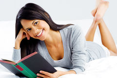 Leisure book woman. Leisure reading woman is comfortable lying on her bed with a book, smiling and happy  on grey background Stock Images