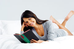 Leisure book woman. Leisure reading woman is comfortable lying on her bed with a book, smiling and happy  on grey background Stock Photography