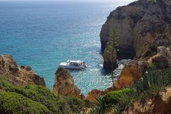 Leisure catamaran with tourists anchored at a bay. Leisure catamaran with tourists anchored at  Martin Barranco Beach on the Algarve coast in southern Portugal Royalty Free Stock Photo