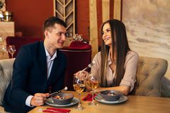 Smiling couple having dinner and drinking white wine at date in restaurant. Leisure, celebration, food and drinks, people and holidays concept - smiling couple Stock Photography