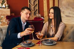 Smiling couple having dinner and drinking white wine at date in restaurant. Leisure, celebration, food and drinks, people and holidays concept - smiling couple Stock Photos