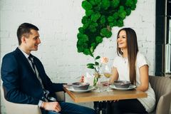 Smiling couple having dinner and drinking white wine at date in restaurant. Leisure, celebration, food and drinks, people and holidays concept - smiling couple Royalty Free Stock Image
