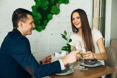Smiling couple having dinner and drinking white wine at date in restaurant. Leisure, celebration, food and drinks, people and holidays concept - smiling couple Stock Image