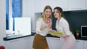 Leisure of cheerful girlfriends during snack and photographed on telephone with meal in arms. At home stock video footage