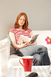 Leisure concept - woman reading a book. A pretty young woman reading a book at home during her leisure time Royalty Free Stock Images